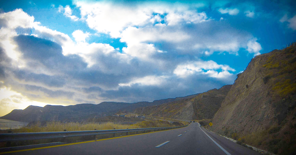 Motorists view of the road curving along the hillside with an expansive cloud-filled sky.