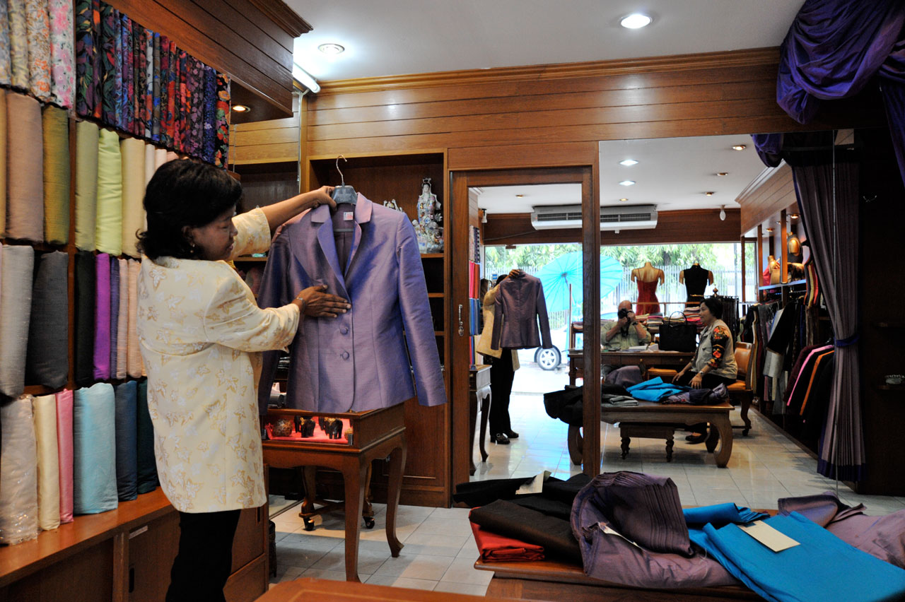Bolts of cloth are shelved and a tailor examines a custom made jacket.