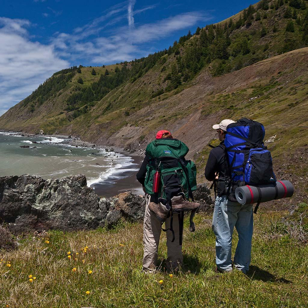 Two campers with backpacking backpacks take in the costal view at Mattole Camp.